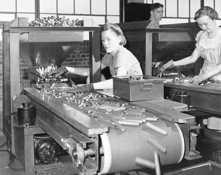FILE - In this June 26, 1942, file photo, women workers at the St. Louis Ordnance plant inspect 50 calibre shell casings. This is the first inspection of the shells after they come through the metal shaping machines. Not since World War II when factories converted from making automobiles to making tanks, Jeeps and torpedos has the entire nation been asked to truly sacrifice for a greater good. (AP Photo, File)