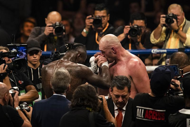 LOS ANGELES, USA - DECEMBER 01: Tyson Fury kisses Deontay Wilder on his hand at the end of WBC Heavyweight Championship at the Staples Center in Los Angeles, California on December 01, 2018. (Photo by Philip Pacheco/Anadolu Agency/Getty Images)