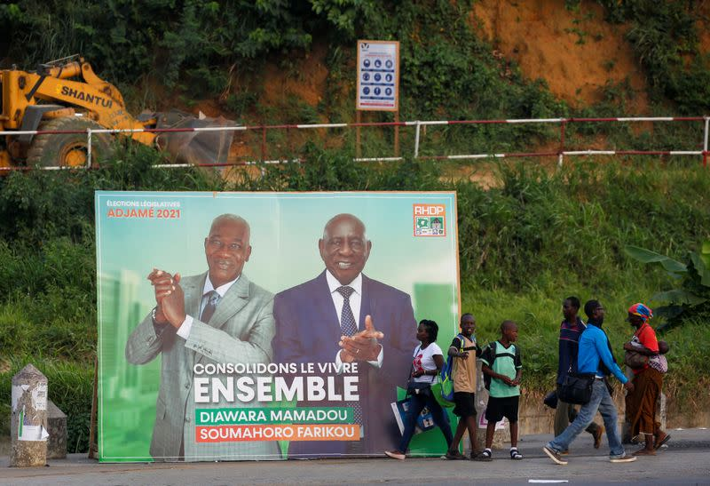 People walk pass next to a campaign bilboard showing the candidats of the ruling coalition party, the Rally of Houphouetists for Democracy and Peace (RHDP) ahead of the legislative election in Abidjan