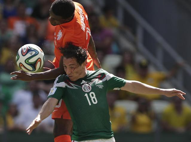 Mexico's Andres Guardado (18) and Netherlands' Georginio Wijnaldum go for a header during the World Cup round of 16 soccer match between the Netherlands and Mexico at the Arena Castelao in Fortaleza, Brazil, Sunday, June 29, 2014. (AP Photo/Marcio Jose Sanchez)