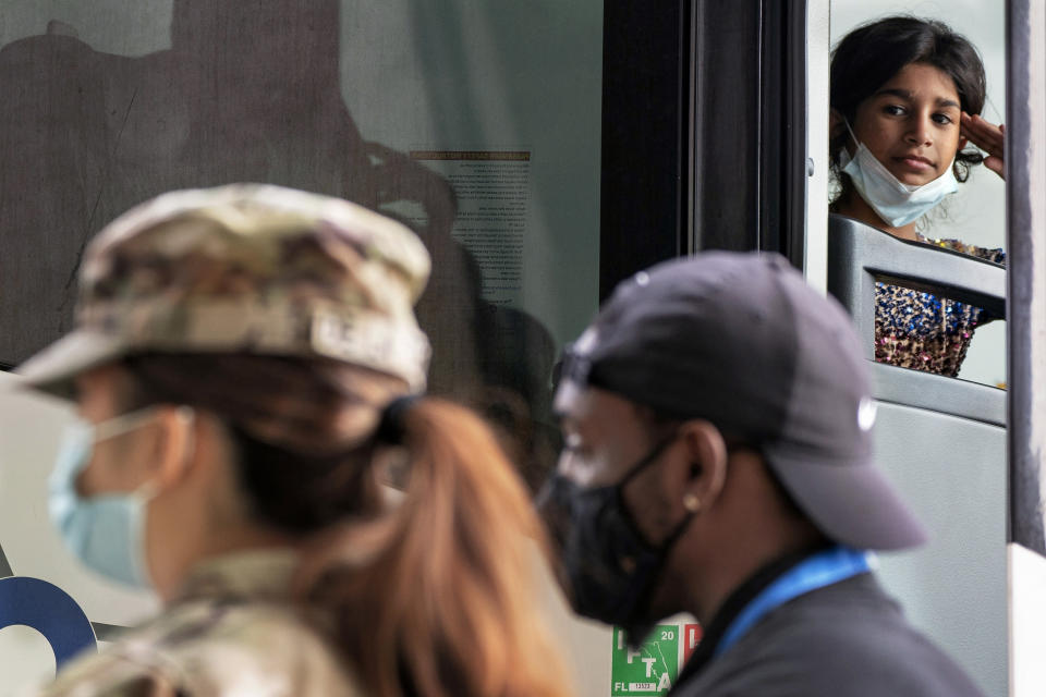 A girl leans against her fingertips while looking out at a female U.S. soldier, as families evacuated from Kabul, Afghanistan, board a bus after they arrived at Washington Dulles International Airport, in Chantilly, Va., on Tuesday, Aug. 31, 2021. (AP Photo/Jacquelyn Martin)