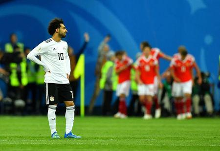 Soccer Football - World Cup - Group A - Russia vs Egypt - Saint Petersburg Stadium, Saint Petersburg, Russia - June 19, 2018 Egypt's Mohamed Salah looks dejected while Russia's Artem Dzyuba celebrates scoring their third goal with team mates REUTERS/Dylan Martinez