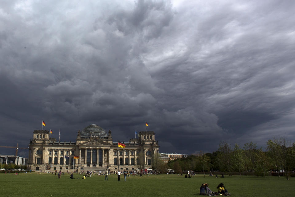 File - In this Tuesday, Aug. 20, 2013 file photo, dark clouds hang over the Reichstag, the German parliament Bundestag building, in Berlin. Hundreds of immigrants are running in Germany's national election on Sunday, raising the possibility of making its next parliament more diverse than ever. While it still might not fully represent the country's overall diversity, where more than a quarter of the population has immigrant roots, it's a step toward a more accurate reflection of society. (AP Photo/Markus Schreiber, File)