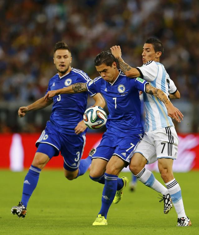 Bosnia's Muhamed Besic (C) fights for the ball with Argentina's Angel Di Maria (R) during their 2014 World Cup Group F soccer match at the Maracana stadium in Rio de Janeiro June 15, 2014. REUTERS/Pilar Olivares (BRAZIL - Tags: SOCCER SPORT WORLD CUP)
