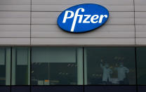 FILE -In this Wednesday, Dec. 2, 2020 file photo, two employees wave from a window at Pfizer Manufacturing in Puurs, Belgium. As soon as it dawned on the continent more than one year ago that the virus would turn into the worst pandemic in a century, the race for a vaccine was on. In securing one, once it was available, the EU could not be as nimble as such a crisis situation demanded. The EU nations got competitive prices, but it took valuable time. (AP Photo/Virginia Mayo, File