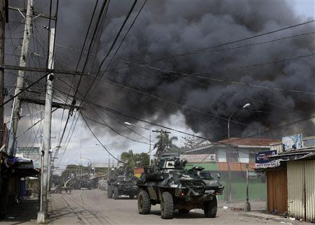 Government soldiers inside armoured vehicles take part in a firefight with Muslim rebels from the MNLF amidst smoke from burning houses in a residential district in Zamboanga city