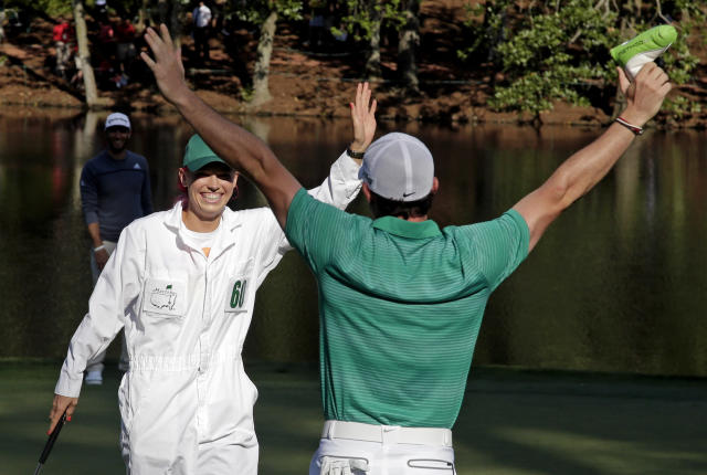 Rory McIlroy, of Northern Ireland, celebrates with his fiancee and tennis player Caroline Wozniacki after Wozniacki putted on the ninth hole during the par three competition at the Masters golf tournament Wednesday, April 9, 2014, in Augusta, Ga.(AP Photo/Chris Carlson)