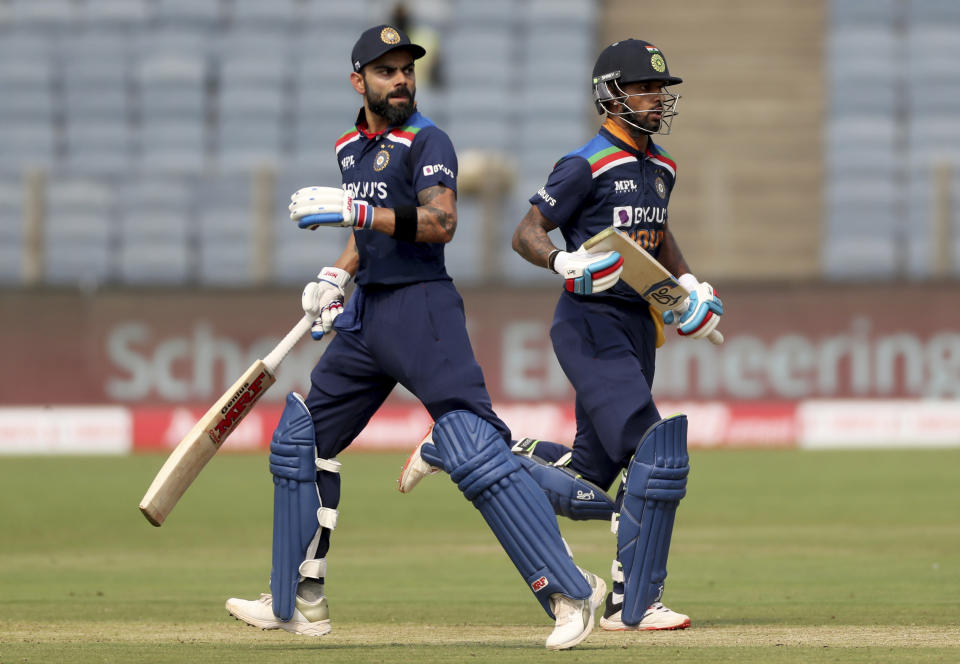 India's captain Virat Kohli, left, and Shikhar Dhawan run between the wickets to score during the first One Day International cricket match between India and England at Maharashtra Cricket Association Stadium in Pune, India, Tuesday, March 23, 2021. (AP Photo/Rafiq Maqbool)