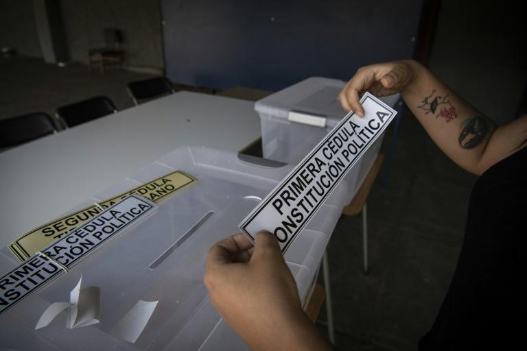 An electoral worker sets up a polling station on the eve of Chile's constitutional referendum in Santiago