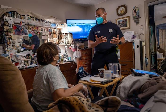 A man in a blue uniform who is wearing a mask speaks to a woman sitting in a recliner in a living room.