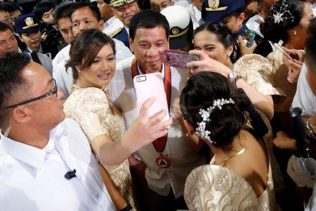 Philippines President Rodrigo Duterte is having his pictures taken with three girls as they attend the ceremony marking the anniversary of the Philippines Coast Guard in Manila, Philippines, October 12, 2016. REUTERS/Damir Sagolj