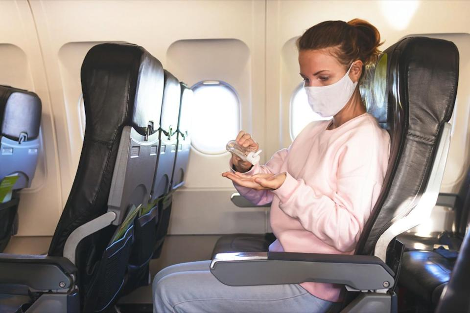 woman in airplane disinfects hands with gel, sanitizer during flight
