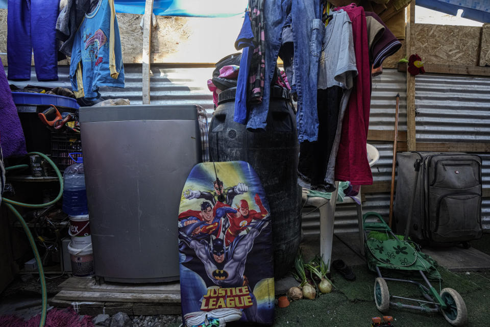 Toys and clothing lay in the home of Haitian migrants in the Dignidad camp where migrants set up homes in Santiago, Chile, Thursday, Sept. 30, 2021. Most Haitian migrants are fleeing earthquakes, hurricanes, political turbulence and poverty in their homeland. (AP Photo/Esteban Felix)