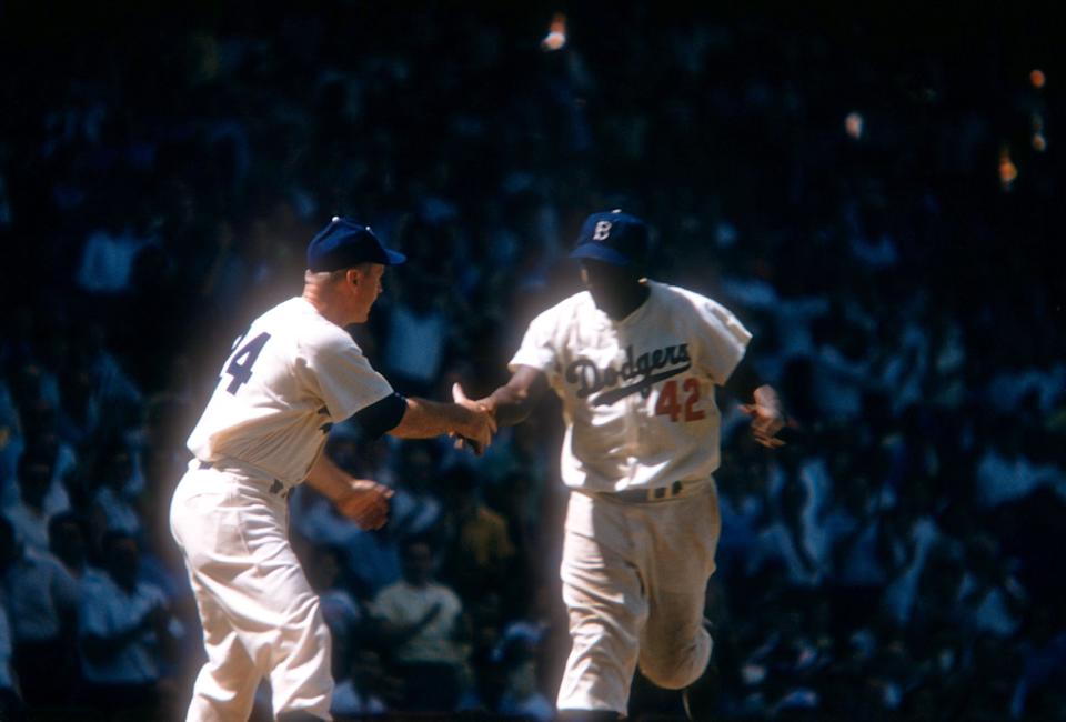 BROOKLYN, NY - JUNE 26:  Jackie Robinson #42 of the Brooklyn Dodgers is congratulated by manager Walter Alston #24 after hitting a homerun during an MLB game against the St. Louis Cardinals on June 26, 1954 at Ebbets Field in Brooklyn, New York.  (Photo by Hy Peskin/Getty Images) (Set Number: X1434)