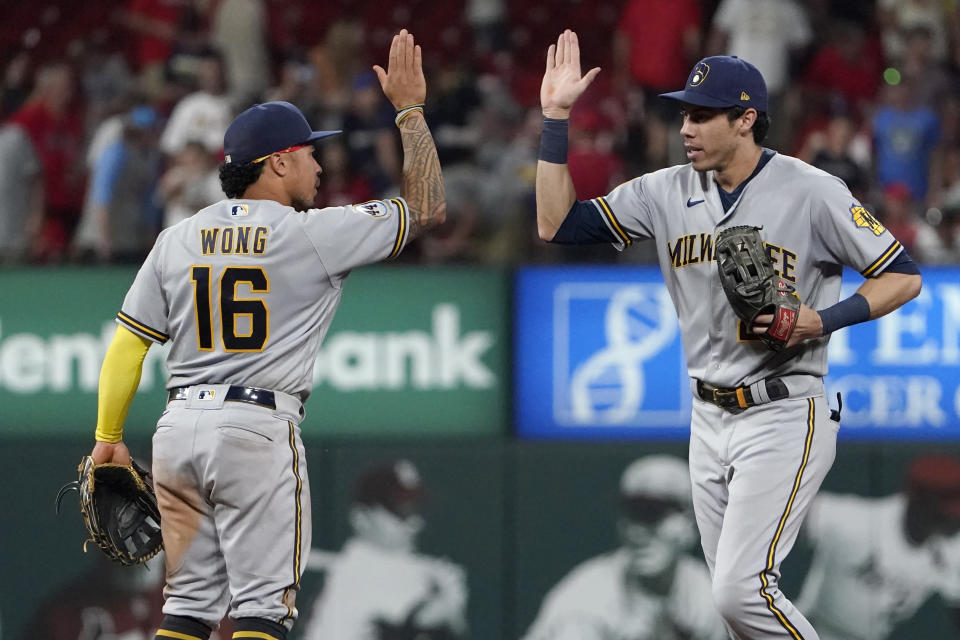 Milwaukee Brewers' Christian Yelich and teammate Kolten Wong (16) celebrate a victory over the St. Louis Cardinals in a baseball game Tuesday, Aug. 17, 2021, in St. Louis. (AP Photo/Jeff Roberson)