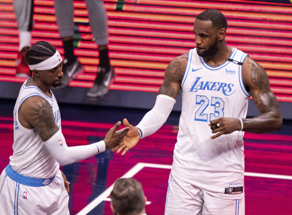 Los Angeles Lakers guard Kentavious Caldwell-Pope, left, and forward LeBron James (23) reacts after defeating the Indiana Pacers in an NBA basketball game in Indianapolis, Saturday, May 15, 2021. (AP Photo/Doug McSchooler)