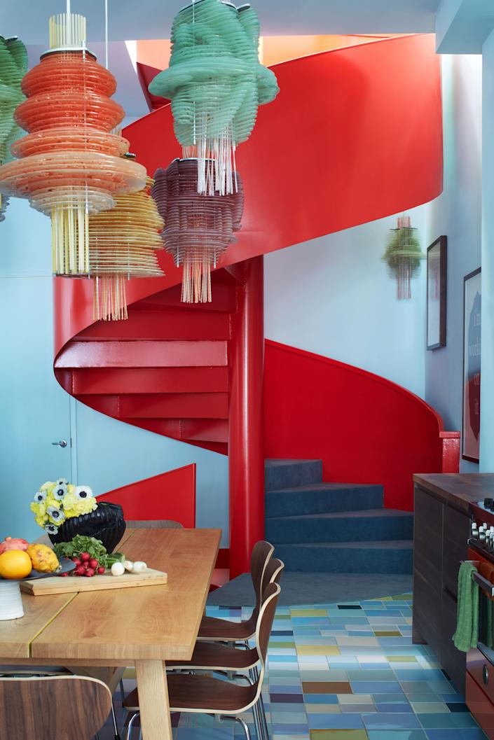 "Pardo replaced the existing staircase with a spiral design in scarlet; the walls are painted in a hand-mixed combination of <a href=""https://www.behr.com/consumer/colors/paint/explore"" rel=""nofollow noopener"" target=""_blank"" data-ylk=""slk:Behr"" class=""link rapid-noclick-resp"">Behr</a> colors."