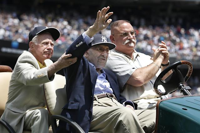Hall of Fame pitcher Whitey Ford, left, helps former teammate and Hall of Famer catcher Yogi Berra as Berra is introduced during the 68th annual Old Timers Day prior to the Baltimore Orioles baseball game against the New York Yankees at Yankee Stadium in New York, Sunday, June 22, 2014. (AP Photo/Kathy Willens)