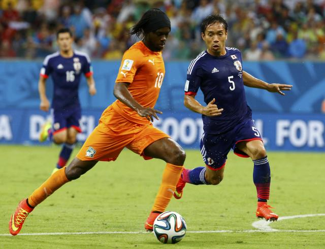 Ivory Coast's Gervinho (L) fights for the ball with Japan's Yuto Nagatomo during their 2014 World Cup Group C soccer match at the Pernambuco arena in Recife June 14, 2014. REUTERS/Stefano Rellandini (BRAZIL - Tags: SOCCER SPORT WORLD CUP)