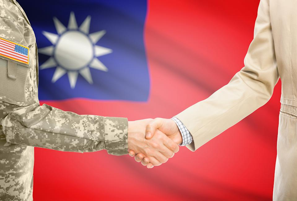 American soldier in uniform and civil man in suit shaking hands with adequate national flag on background - Republic of China - Taiwan