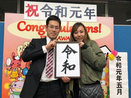 Kenya Fujisaki (29) and his wife Saya (29) hold a placard with the name of the new era Reiwa as they pose for a photograph in front of a panel set up for a commemorative photos, after registering marriage at the head office of Tokyo's Edogawa ward in Tokyo, Japan, May 1, 2019, on the first day of Japan's new Reiwa imperial era. REUTERS/Kiyoshi Takenaka