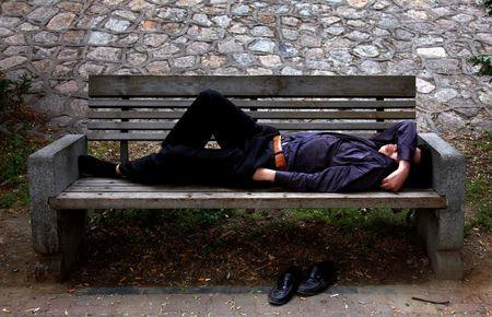 A man sleeps on a park bench with his hand in his pocket in Beijing