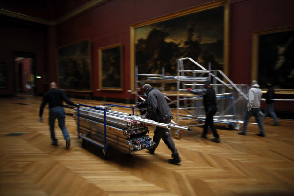 Workers at the Louvre museum pull a scaffolding in Paris, Tuesday, Feb. 9, 2021. Though empty corridors and vacant galleries are a grim sight for frustrated art-lovers, they are a golden opportunity to do works of renovation, refurbishment and re-ordering that were simply not possible with the around 10 million visitors per year. (AP Photo/Thibault Camus)