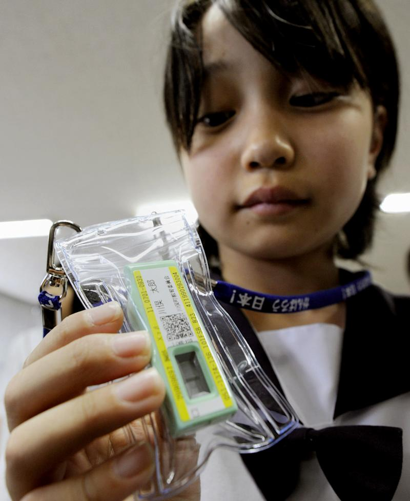 In this June 21, 2011 photo, a student holds a radiation meter donated by a local university,  in Kawamata town, Fukushima prefecture, northeastern Japan.  The town distributed some 1,500 dosimeters to children between the ages of four and 15 and teachers in the town.  Radiation meters will be distributed to about 34,000 children living in the largest city of Fukushima, near the tsunami-damaged Fukushima Dai-ichi nuclear plant to monitor their exposure levels, a city official said Tuesday, June 28, 2011.   (AP Photo/Kyodo News) JAPAN OUT, MANDATORY CREDIT, NO LICENSING IN CHINA, FRANCE, HONG KONG, JAPAN AND SOUTH KOREA