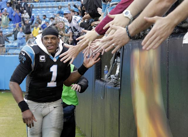 Carolina Panthers' Cam Newton (1) celebrates with fans after an NFL football game against the New Orleans Saints in Charlotte, N.C., Sunday, Dec. 22, 2013. The Panthers won 17-13. (AP Photo/Bob Leverone)