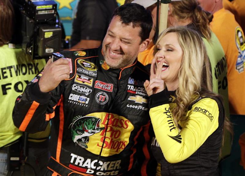 Tony Stewart, left, takes a selfie with Miss Sprint, right, after being introduced before the NASCAR Sprint All-Star auto race at Charlotte Motor Speedway in Concord, N.C., Saturday, May 17, 2014