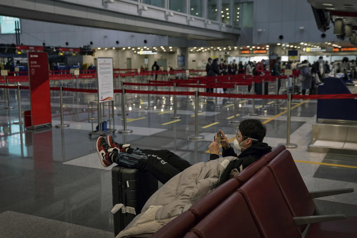 A man wearing a face mask to curb the spread of the coronavirus sits on a bench playing a game on his smartphone as passengers line up to check in their luggage at a quiet departure hall of the Beijing Capital International Airport in Beijing, Wednesday, Feb. 3, 2021. Amid fears of new variants of the virus, new restrictions on movement have hit just as people start to look ahead to what is usually a busy time of year for travel. (AP Photo/Andy Wong)