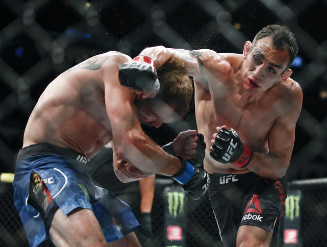 FILE - In this June 8, 2019, file photo, Tony Ferguson punches Donald Cerrone during their lightweight bout at UFC 238 in Chicago. The UFC says Ferguson will fight Justin Gaethje for the interim lightweight title in the main event of UFC 249 on May 9, 2020. (AP Photo/Kamil Krzaczynski, File)