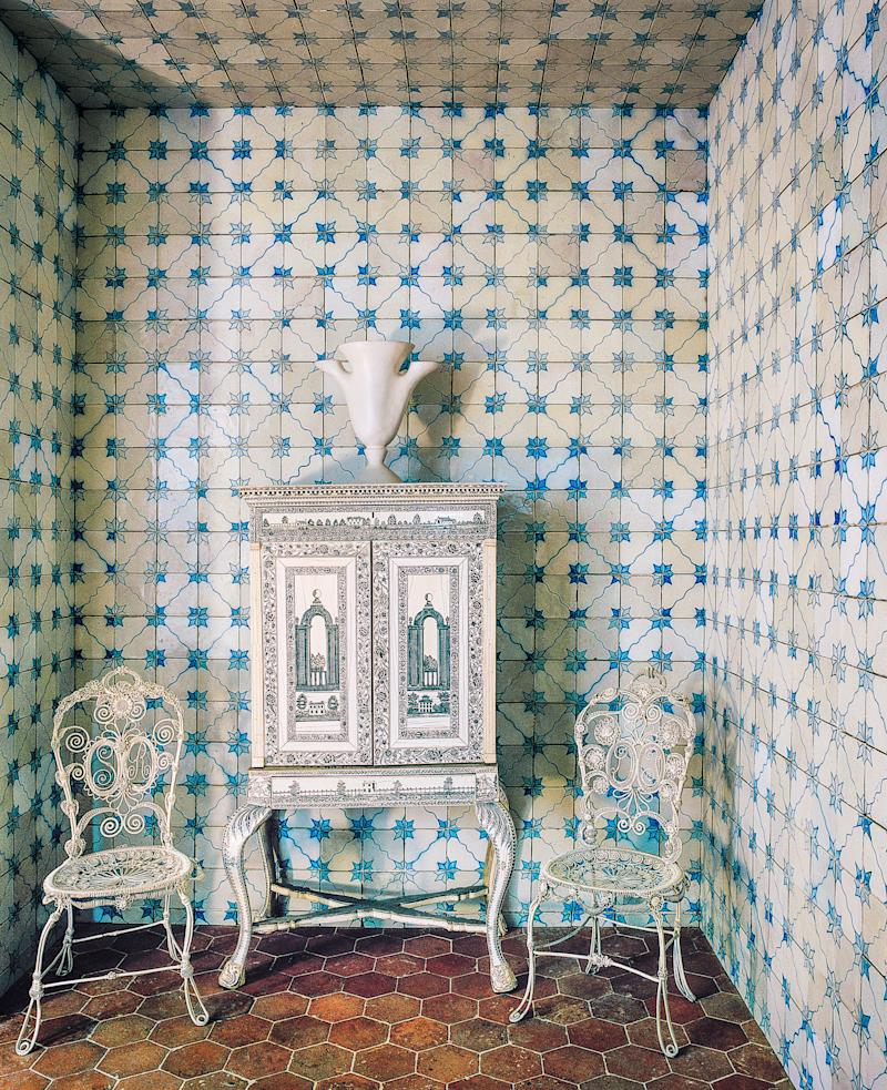 Azulejo tiles cover the walls of the second entry. 19th-century chairs from Madeleine Castaing; 18th-century ivory cabinet.