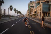 People ride on a car-free road during Yom Kippur, the holiest day in the Jewish year, during a nationwide three-week lockdown to curb the spread of the coronavirus, in Tel Aviv, Israel, Sunday, Sept. 27, 2020. (AP Photo/Oded Balilty)