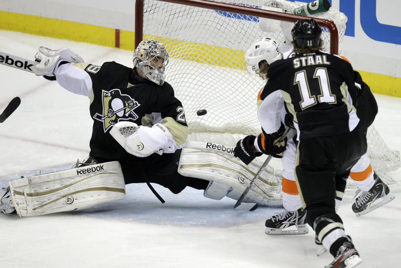 Philadelphia Flyers' Jakub Voracek, right rear, scores a goal in overtime past Pittsburgh Penguins goalie Marc-Andre Fleury (29) and Penguins' Jordan Staal (11) during Game 1 of the opening-round NHL hockey playoff series Wednesday, April 11, 2012, in Pittsburgh. The Flyers won 4-3. (AP Photo/Gene J. Puskar)