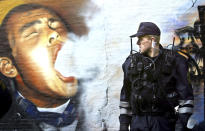 """FILE - In this Tuesday, March 16, 2004 file photo, a member of the Copenhagen police patrols the enclave of Christiania in Copenhagen, Denmark. Copenhagen's Christiania neighborhood is turning 50 and after years of not always peaceful coexistence with the authorities, the counter-culture enclave wants to maintain its reputation as a """"free-wheeling society"""" of hash dealers, political idealists, and aging hippies. One resident says the oasis has"""" become more and more an established part"""" of the Danish capital. It all started in 1971, when a small counterculture newspaper needed an outrageous story for its front page and staged an """"invasion"""" of an abandoned 18-century navy base. (AP Photo/John McConnico, File)"""