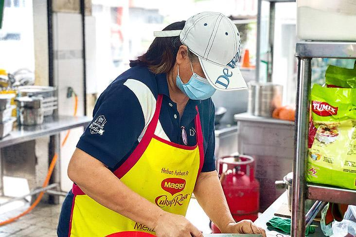 Lily Chang preparing the toppings for Penang prawn mee.