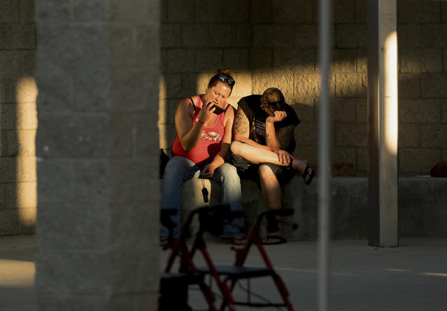 <p>Josh Cornelison and Sharon Reitan rest outside an evacuation shelter for people affected by a wildfire on Sunday, July 9, 2017, in Oroville, Calif. The couple lost their home as the Wall tore through a mountain community Friday. (AP Photo/Noah Berger) </p>
