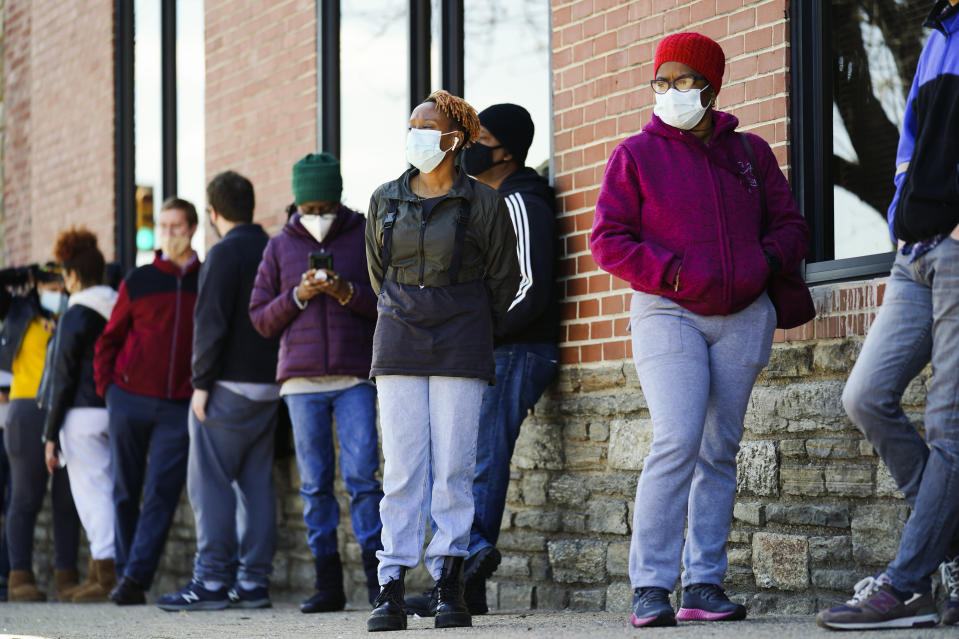 People wearing face masks as a precaution against the coronavirus wait in line to receive COVID-19 vaccines at a site in Philadelphia, Monday, March 29, 2021. (AP Photo/Matt Rourke)