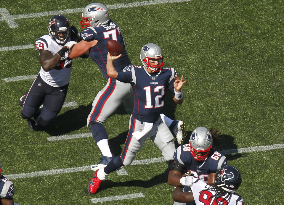 New England Patriots quarterback Tom Brady passes under pressure from Houston Texans defenders Whitney Mercilus and Jadeveon Clowney during the first half on Sunday. (AP Photo)