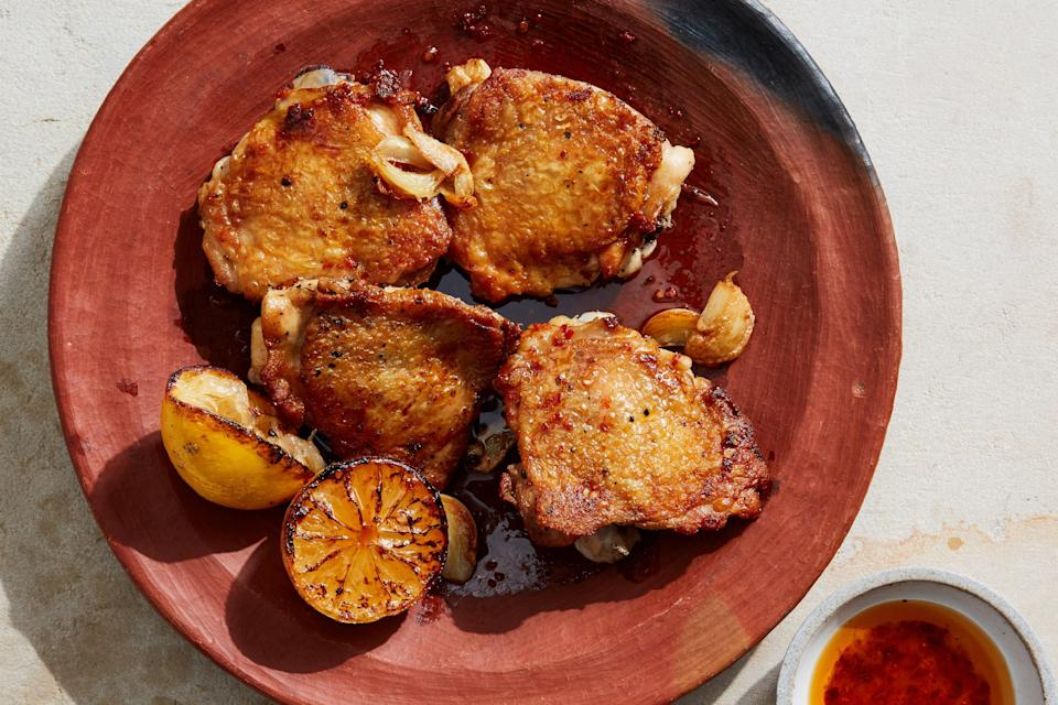 """Zingy white vinegar does double duty here, tenderizing chicken thighs while giving them a tart flavor accentuated by a super-easy charred lemon–garlic sauce. These baked chicken thighs are full of flavor. <a href=""""https://www.epicurious.com/recipes/food/views/lemon-chicken-thighs?mbid=synd_yahoo_rss"""" rel=""""nofollow noopener"""" target=""""_blank"""" data-ylk=""""slk:See recipe."""" class=""""link rapid-noclick-resp"""">See recipe.</a>"""