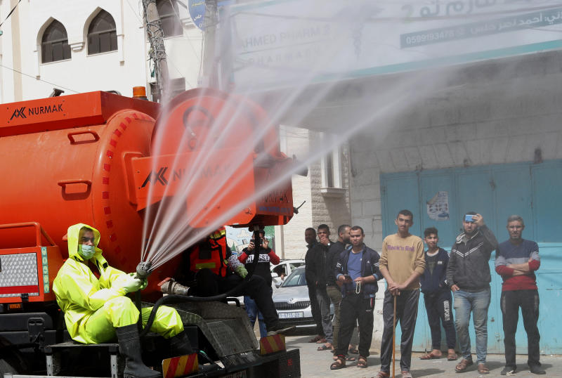 Residents watch workers wearing protective gear spray disinfectant as a precaution against the coronavirus, at the main road of closed market of Shijaiyah neighborhood in Gaza City, Friday, March 27, 2020. Gaza municipality close all the weekly Friday markets in Gaza starting from today. (AP Photo/Adel Hana)