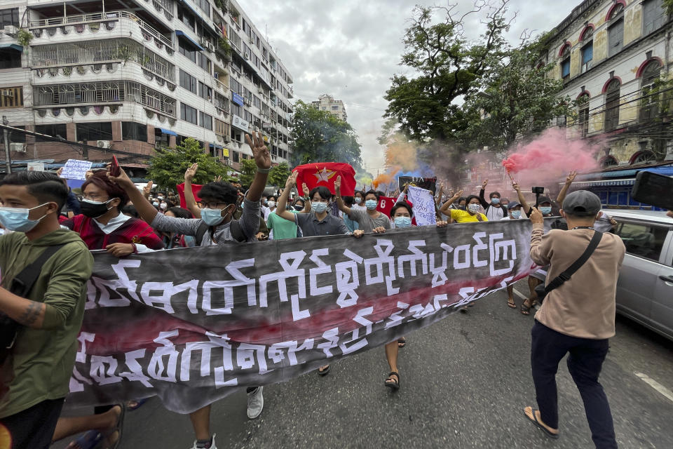 """Students protest against the February military takeover by the State Administration Council as they march at Kyauktada township in Yangon, Myanmar on Wednesday July 7, 2021. Sign reads """"Hold spirit and fight. Defeat the dictatorship in any way you can."""" (AP Photo)"""