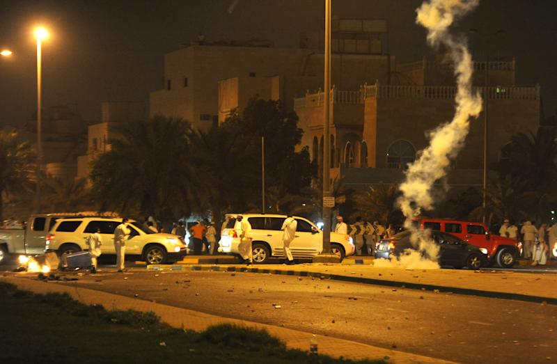 In this Wednesday, April 17, 2013 photo, supporters of former MP Musallam al-Barrack demonstrate near his house in Al Andalous, Kuwait. Police used tear gas and stun grenades to disperse the crowds. Outside a palm-shaded villa in suburban Kuwait City, government security forces are taunted and defied each night by supporters of a former lawmaker ordered to prison for insulting the emir of this tiny nation.(AP Photo/Nasser Waggi)