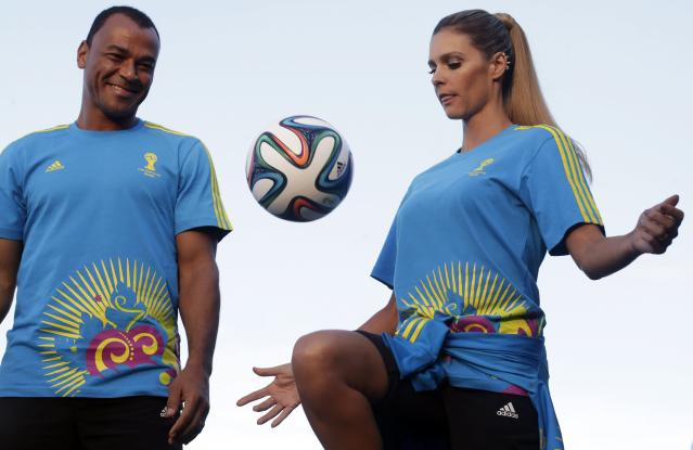Former Brazilian soccer player Cafu (L) looks at Brazilian model Fernanda Lima as they present the uniforms for World Cup 2014 volunteers during Fashion Rio in Rio de Janeiro April 10, 2014. REUTERS/Ricardo Moraes (BRAZIL - Tags: FASHION SPORT SOCCER WORLD CUP)