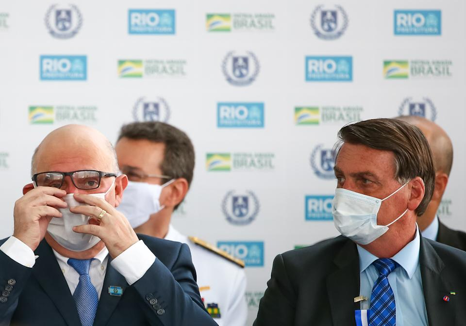 RIO DE JANEIRO, BRAZIL - AUGUST 14: Minister of Education Milton Ribeiro (L) adjusts his face mask next to President of Brazil Jair Bolsonaro during the opening of the Escola Civico-Militar General Abreu on August 14, 2020 in Rio de Janeiro, Brazil. The civic-military school inaugurated by the city of Rio de Janeiro has a capacity for 500 students. Two other units will be added to the complex, which will be launched by the end of the year. Civic-military schools are non-militarized institutes with retired military agents as tutors, a model advocated by the government of Jair Bolsonaro. (Photo by Buda Mendes/Getty Images)
