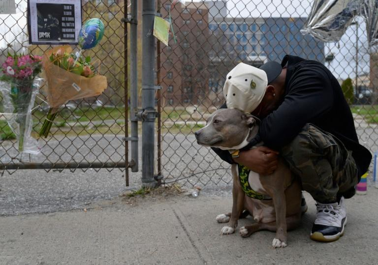 A man holds his dog as he reacts at a makeshift memorial for hip-hop star DMX, who was well-known for his love of canines