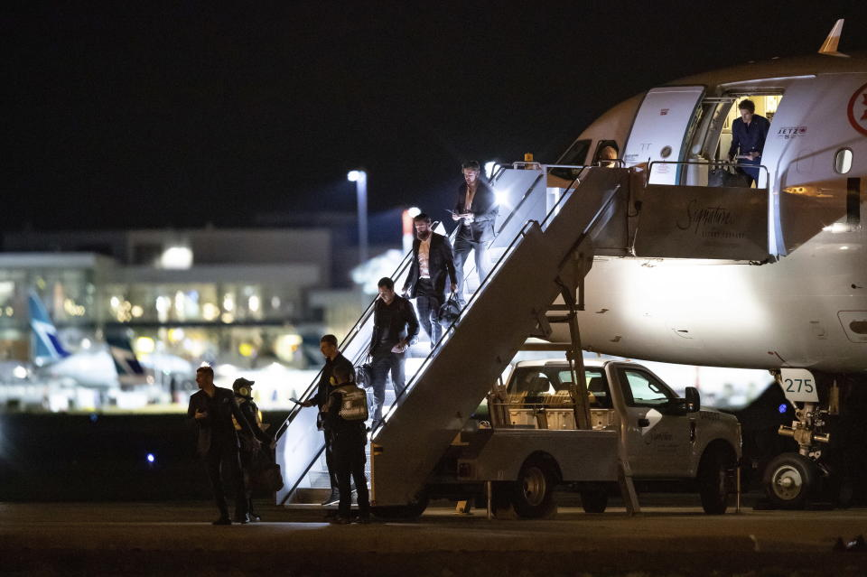 Vancouver Canucks players step off the NHL hockey team's charter plane after returning from Phoenix, at Vancouver International Airport in Richmond, British Columbia, Thursday, March 12, 2020. From bottom left are Louis Domingue, Tyler Myers, Bo Horvat, Jordie Benn, Tanner Pearson and Loui Eriksson. The NHL has suspended the season due to concerns about the new coronavirus. (Darryl Dyck/The Canadian Press via AP)