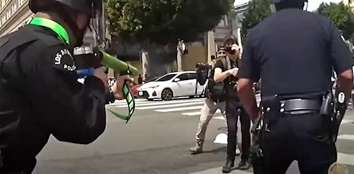 Newly-released body-camera footage from protests in Los Angeles this summer shows Los Angeles police officers yank a large protest sign from the hands of a man in a Hollywood intersection, shove him backwards as he puts his hands up, then shoot him in the groin with a projectile at close range.