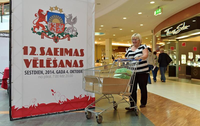 A woman pushes her shopping trolley by a placard announcing general elections in Riga on October 3, 2014